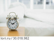 Купить «Retro alarm clock standing on a bedside table», фото № 30018982, снято 9 июля 2013 г. (c) Wavebreak Media / Фотобанк Лори