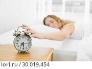 Купить «Pretty calm blonde lying in bed turning off alarm clock», фото № 30019454, снято 11 июля 2013 г. (c) Wavebreak Media / Фотобанк Лори