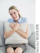Купить «Cute chic businesswoman holding a pillow sitting on couch», фото № 30019978, снято 17 июля 2013 г. (c) Wavebreak Media / Фотобанк Лори