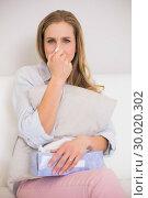 Купить «Frowning casual blonde sitting on couch blowing nose», фото № 30020302, снято 30 мая 2013 г. (c) Wavebreak Media / Фотобанк Лори