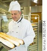 Купить «Mature head chef holding some baguettes », фото № 30021054, снято 14 августа 2013 г. (c) Wavebreak Media / Фотобанк Лори