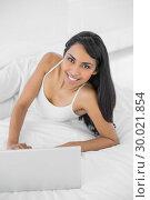 Купить «Content woman using her notebook lying on her bed», фото № 30021854, снято 4 июля 2013 г. (c) Wavebreak Media / Фотобанк Лори