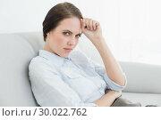 Купить «Portrait of a serious well dressed woman sitting on sofa», фото № 30022762, снято 12 июля 2013 г. (c) Wavebreak Media / Фотобанк Лори