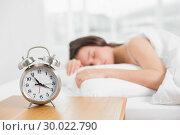 Купить «Woman in bed with alarm clock in foreground», фото № 30022790, снято 16 июля 2013 г. (c) Wavebreak Media / Фотобанк Лори
