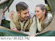 Smiling couple lying in tent after a hike. Стоковое фото, агентство Wavebreak Media / Фотобанк Лори