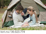 Купить «Young couple with a map lying in tent», фото № 30023774, снято 20 августа 2013 г. (c) Wavebreak Media / Фотобанк Лори