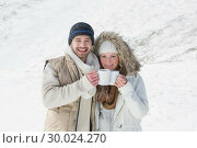 Купить «Couple in warm clothing with coffee cups on snowed landscape», фото № 30024270, снято 22 августа 2013 г. (c) Wavebreak Media / Фотобанк Лори
