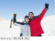 Купить «Couple raising hands with ski board on snow in background», фото № 30024362, снято 22 августа 2013 г. (c) Wavebreak Media / Фотобанк Лори