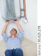 Купить «Technician servicing an hot water heater», фото № 30025278, снято 25 июля 2013 г. (c) Wavebreak Media / Фотобанк Лори