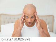 Купить «Close up of bald man suffering from headache in bed», фото № 30026878, снято 1 августа 2013 г. (c) Wavebreak Media / Фотобанк Лори