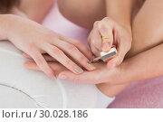 Купить «Mid section of a young woman painting friends nails», фото № 30028186, снято 16 августа 2013 г. (c) Wavebreak Media / Фотобанк Лори