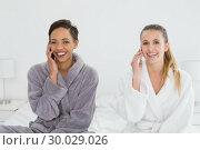 Купить «Female friends in bathrobes using phones on bed», фото № 30029026, снято 13 августа 2013 г. (c) Wavebreak Media / Фотобанк Лори