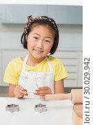 Купить «Smiling young girl holding cookie mold in kitchen», фото № 30029942, снято 29 августа 2013 г. (c) Wavebreak Media / Фотобанк Лори
