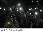 Купить «День православной молодежи в Одинцово. Зрительный зал с включёнными фонарями мобильного телефона», эксклюзивное фото № 30030782, снято 19 февраля 2019 г. (c) Дмитрий Неумоин / Фотобанк Лори