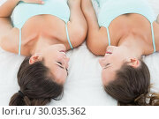 Купить «Female friends in teal tank tops lying in bed», фото № 30035362, снято 14 августа 2013 г. (c) Wavebreak Media / Фотобанк Лори