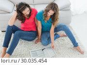 Купить «Female friends reading a book in the living room», фото № 30035454, снято 14 августа 2013 г. (c) Wavebreak Media / Фотобанк Лори