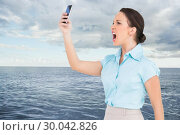 Composite image of angry classy businesswoman yelling at her smartphone. Стоковое фото, агентство Wavebreak Media / Фотобанк Лори