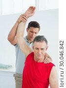 Купить «Physiotherapist stretching a mature mans arm», фото № 30046842, снято 4 октября 2013 г. (c) Wavebreak Media / Фотобанк Лори