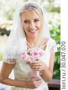Купить «Happy bride in a veil holding her rose bouquet», фото № 30047070, снято 9 октября 2013 г. (c) Wavebreak Media / Фотобанк Лори