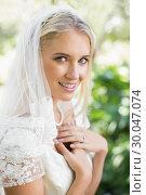 Купить «Blonde smiling bride in a veil holding her hands to her chest», фото № 30047074, снято 9 октября 2013 г. (c) Wavebreak Media / Фотобанк Лори