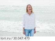 Купить «Casual woman laughing at beach», фото № 30047470, снято 10 октября 2013 г. (c) Wavebreak Media / Фотобанк Лори