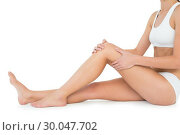 Купить «Side view of a fit young woman with knee pain», фото № 30047702, снято 15 октября 2013 г. (c) Wavebreak Media / Фотобанк Лори