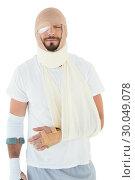 Купить «Young man with head tied up in bandage and broken hand», фото № 30049078, снято 16 октября 2013 г. (c) Wavebreak Media / Фотобанк Лори