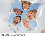 Купить «Happy volunteers forming a huddle against blue sky», фото № 30050026, снято 4 ноября 2013 г. (c) Wavebreak Media / Фотобанк Лори