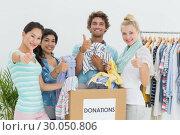 Купить «People with clothes donation gesturing thumbs up», фото № 30050806, снято 5 ноября 2013 г. (c) Wavebreak Media / Фотобанк Лори