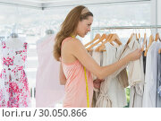 Купить «Beautiful fashion designer looking at clothes on rack», фото № 30050866, снято 5 ноября 2013 г. (c) Wavebreak Media / Фотобанк Лори