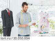 Купить «Fashion designer looking at sketch in the studio», фото № 30050894, снято 5 ноября 2013 г. (c) Wavebreak Media / Фотобанк Лори