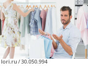 Купить «Bored man with shopping bags while woman by clothes rack», фото № 30050994, снято 5 ноября 2013 г. (c) Wavebreak Media / Фотобанк Лори