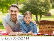Купить «Smiling father with daughter lying on grass in park», фото № 30052114, снято 8 ноября 2013 г. (c) Wavebreak Media / Фотобанк Лори