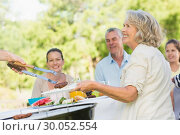 Extended family dining at outdoor table. Стоковое фото, агентство Wavebreak Media / Фотобанк Лори