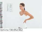 Купить «Side view of a beautiful young woman with back pain», фото № 30052962, снято 1 октября 2013 г. (c) Wavebreak Media / Фотобанк Лори