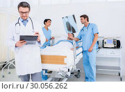 Купить «Doctors holding reports by patient at hospital», фото № 30056262, снято 2 ноября 2013 г. (c) Wavebreak Media / Фотобанк Лори