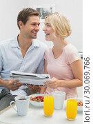 Couple reading newspaper while having breakfast at home. Стоковое фото, агентство Wavebreak Media / Фотобанк Лори
