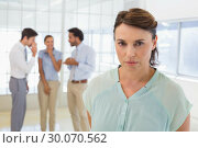 Купить «Colleagues gossiping with sad businesswoman in foreground», фото № 30070562, снято 19 декабря 2013 г. (c) Wavebreak Media / Фотобанк Лори