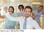 Купить «Cheerful young business colleagues cheering», фото № 30070794, снято 19 декабря 2013 г. (c) Wavebreak Media / Фотобанк Лори