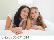 Купить «Mother with cute daughter lying in bed», фото № 30071014, снято 18 декабря 2013 г. (c) Wavebreak Media / Фотобанк Лори