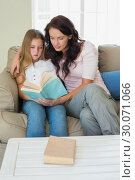 Купить «Girl and mother reading novel on sofa», фото № 30071066, снято 18 декабря 2013 г. (c) Wavebreak Media / Фотобанк Лори
