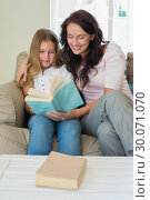 Купить «Girl and mother reading novel on sofa», фото № 30071070, снято 18 декабря 2013 г. (c) Wavebreak Media / Фотобанк Лори