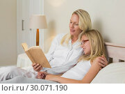 Купить «Mother and daughter reading novel in bed», фото № 30071190, снято 18 декабря 2013 г. (c) Wavebreak Media / Фотобанк Лори