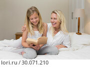 Купить «Woman looking at daughter reading novel in bed», фото № 30071210, снято 18 декабря 2013 г. (c) Wavebreak Media / Фотобанк Лори