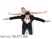 Купить «Groom with arms outstretched carrying bride on back», фото № 30071402, снято 8 октября 2013 г. (c) Wavebreak Media / Фотобанк Лори