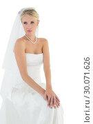 Купить «Thoughtful bride sitting against white background», фото № 30071626, снято 8 октября 2013 г. (c) Wavebreak Media / Фотобанк Лори