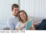 Купить «Young couple reading book on couch», фото № 30071774, снято 17 декабря 2013 г. (c) Wavebreak Media / Фотобанк Лори