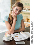 Smiling woman with coffee cup reading magazine in coffee shop. Стоковое фото, агентство Wavebreak Media / Фотобанк Лори