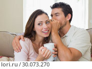 Man whispering secret into a happy womans ear in living room. Стоковое фото, агентство Wavebreak Media / Фотобанк Лори