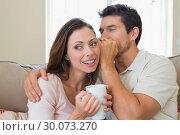 Купить «Man whispering secret into a happy womans ear in living room», фото № 30073270, снято 12 декабря 2013 г. (c) Wavebreak Media / Фотобанк Лори